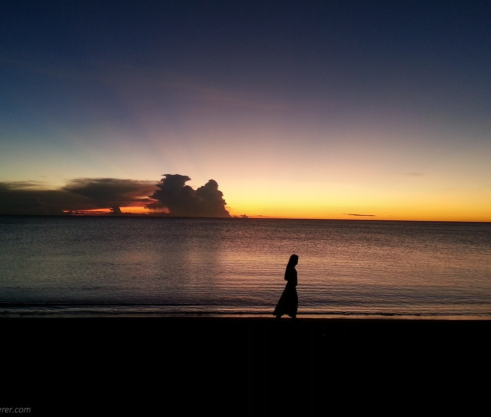 A lady in silhouette walking along the beach shore under the sunset